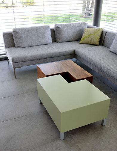 שולחן הסלון תוכנן כשתי יחידות נפרדות, אחת בפורניר אגוז והשניה בצבע, שניתן לקרב לכל צד של הספה הארוכה, או להצמיד למלבן מדויק. בצידו הפנימי מגירות לסכו