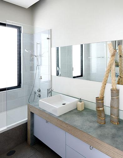שירותי אורחים עם כיור מונח, משטח המורכב משכבות של סנדוויץ', וסל כביסה מתחת לכיור.