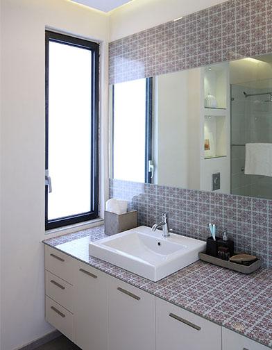 חדר הרחצה של בעלי הבית. משטח הכיור וחיפוי הקיר עשויים זכוכית מודפסת, כשבתוכה משובצת מראה.
